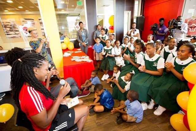 Channon Thompson of the TT National Women's Volleyball team which qualified for the world championship in Japan, reads to the children.