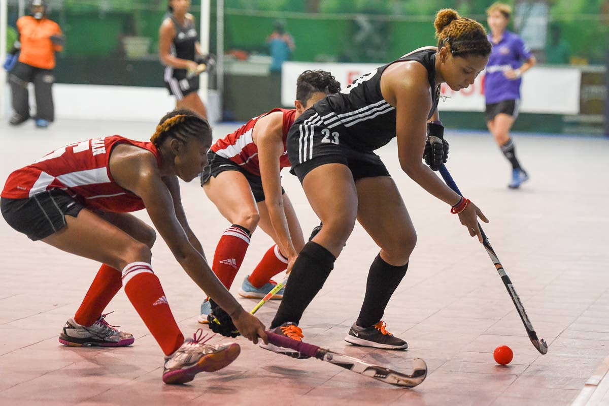 Trinidad and Tobago's Jordan Viera, right, is marked by two Guyanese players in their Pan Am Indoor Cup match yesterday at Cliff Anderson Sports Hall, Georgetown, Guyana.