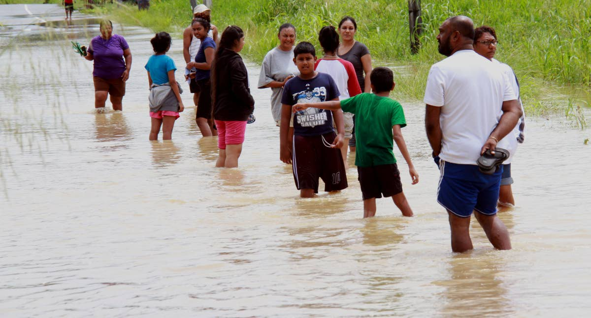 Residents of Siew Trace, Debe, walk through flood waters after being forced to leave their homes.