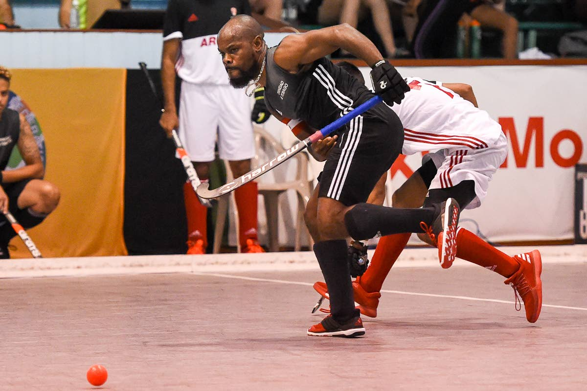 Trinidad and Tobago captain Solomon Eccles makes a pass during a Pan Am Indoor Hockey match against Canada yesterday at the Cliff Anderson Sports Hall, Georgetown, Guyana.