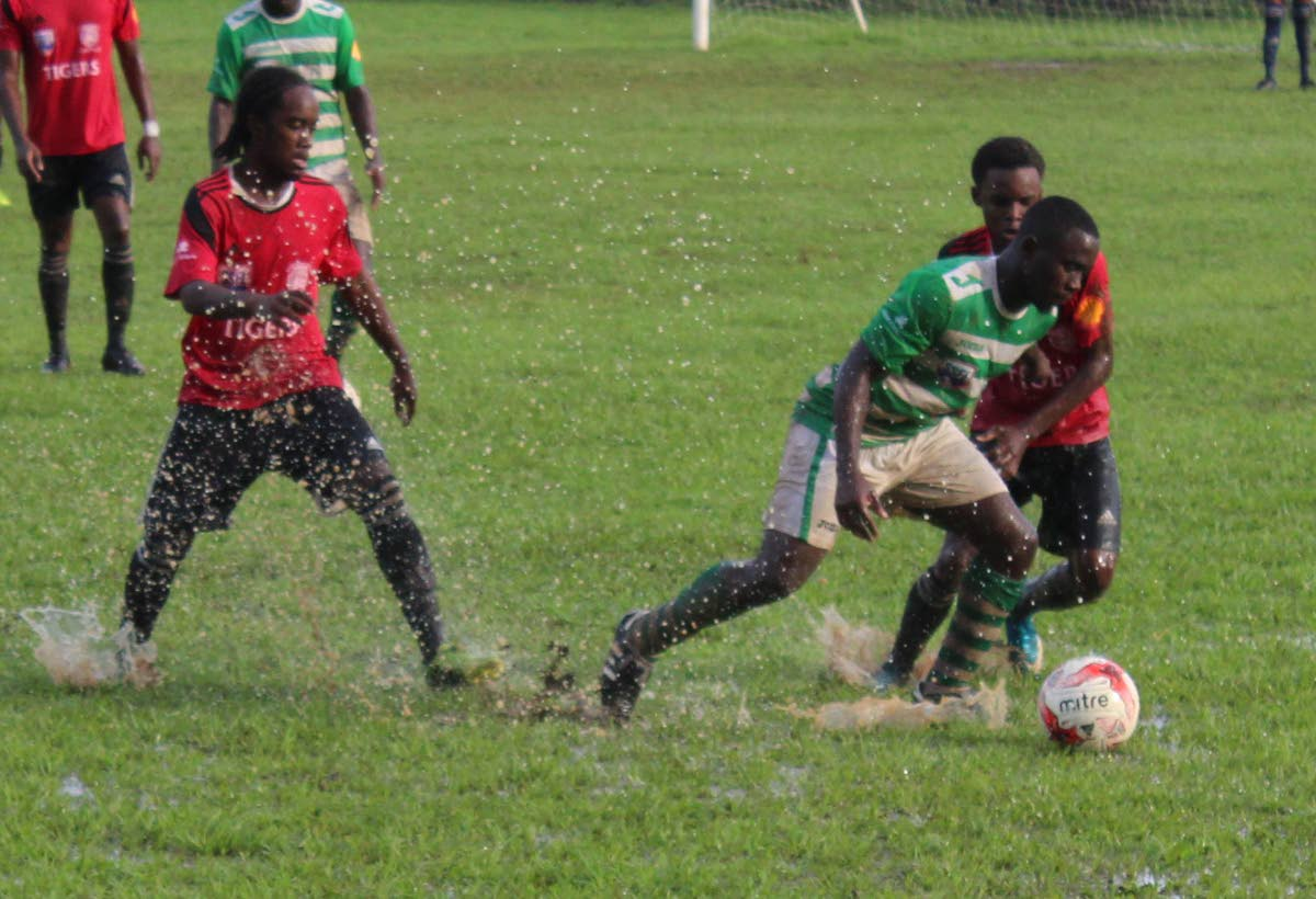 Samuel Anthony (centre) of St Augustine tries to evade the challenges of St Anthony's Che Benny (left) and Quinn Frederick during yesterday's SSFL Premier Division encounter at St Augustine.