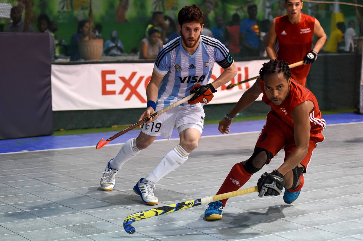Akim Toussaint (right) of Trinidad and Tobago chases after a ball while Argentina captain Joaquin Gonzalez looks on during last evening's final of the Indoor Pan Am Hockey Cup. PHOTO COURTESY PAN AM HOCKEY FEDERATION.