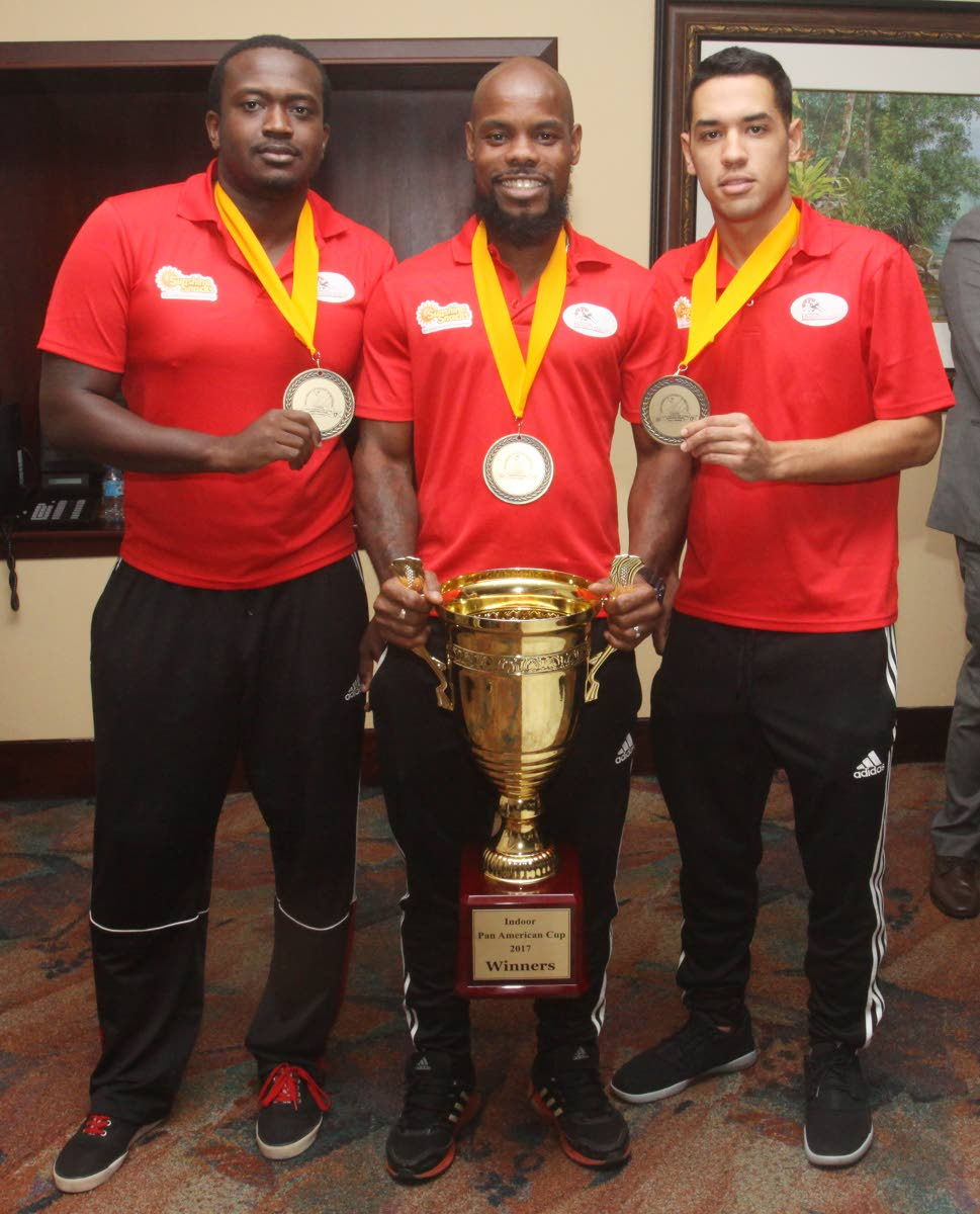 Trinidad and Tobago hockey goalkeeper Ron Alexander, left, Solomon Eccles, centre, and top scorer Jordan Vierra, pose with the Pan Am Indoor Cup at the VIP Lounge, Piarco International Airport, yesterday.