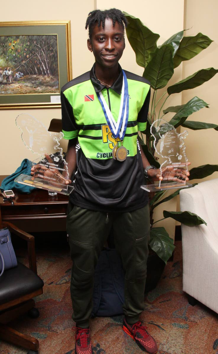 National cyclist Teneil Campbell shows off her Caribbean Road Cycling trophies yesterday.