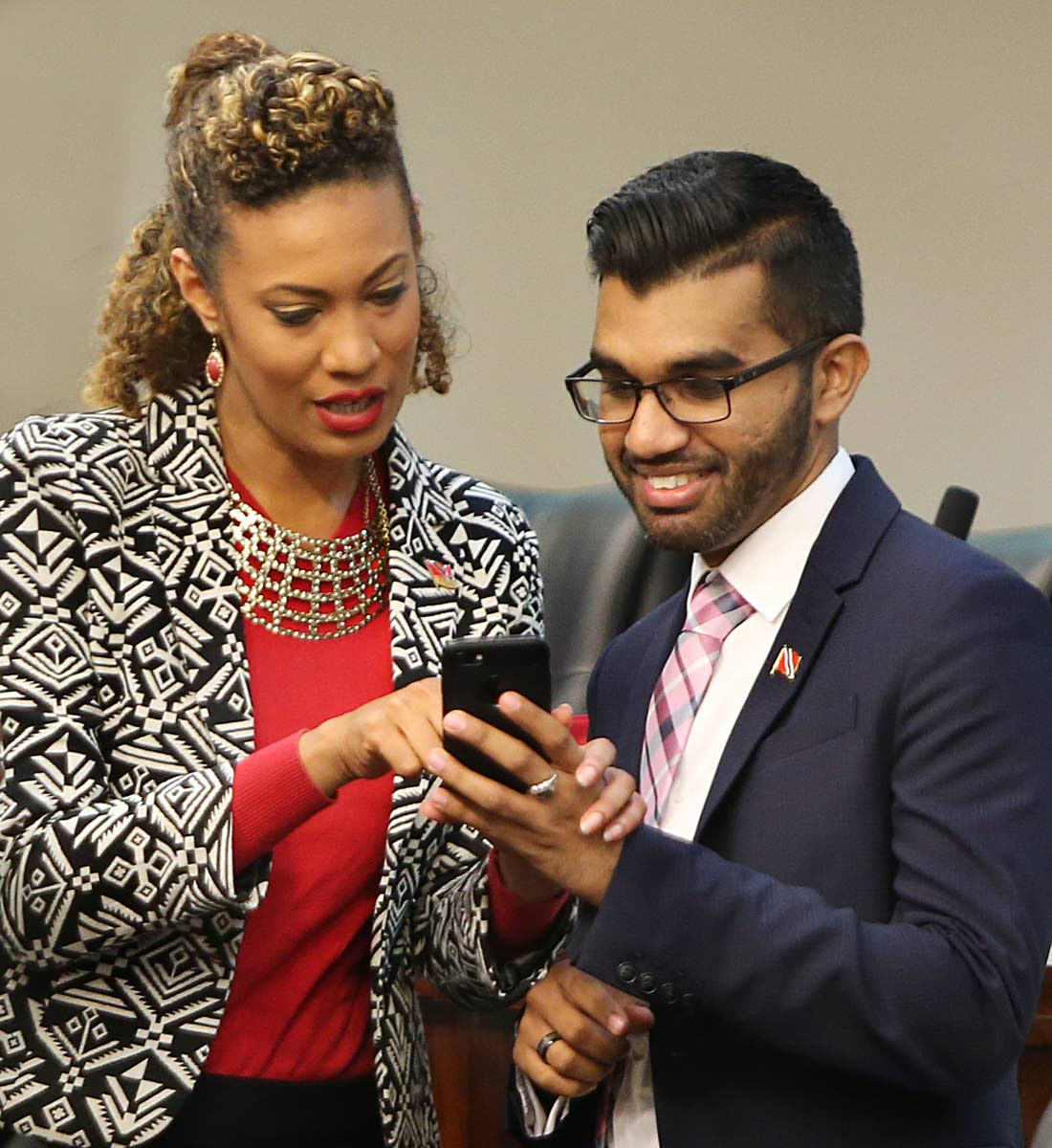 CELLS OFF: UNC Senators Khadijah Ameen and Saddam Hosein check Hosein's cellphone during the lunch break in the Upper House. Independent senator Stephen Creese had to temporarily leave the Parliament during yesterday's budget debate after his cellphone rang out to the tune of Fay Ann Lyons-Alvarez' Get On.