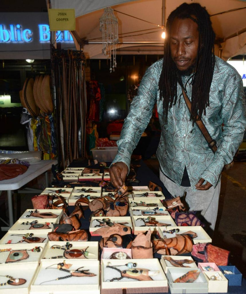 Entrepreneur John Cooper shows his handcrafted leather bands at the Tobago Street Fair on Friday night in Crown Point.