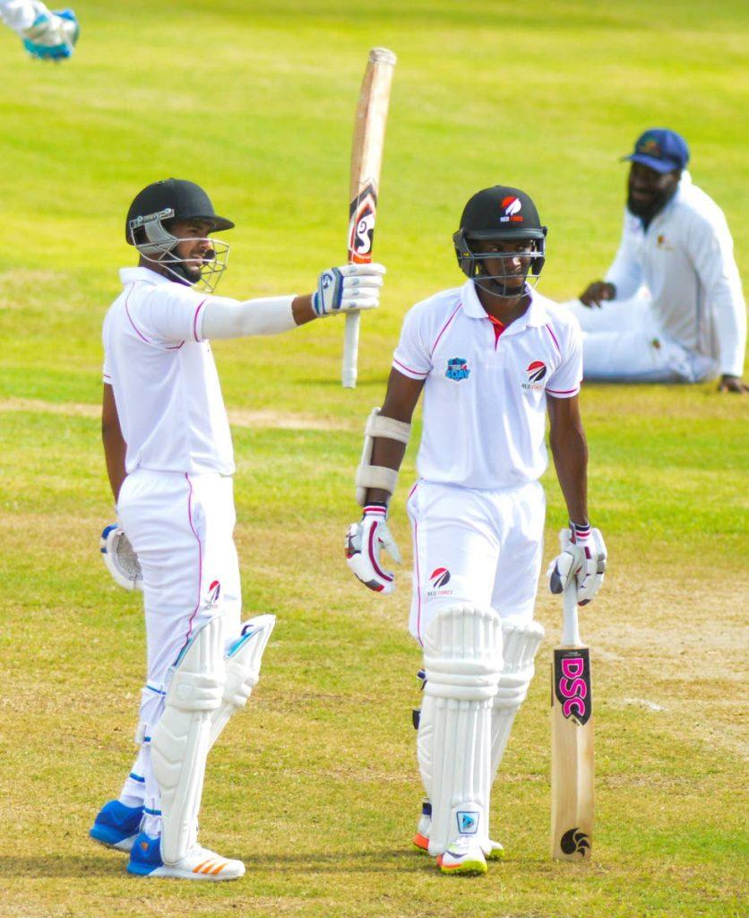 Trinidad and Tobago's Amir Jangoo, left, raises his bat to celebrate his half-century as teammate Jeremy Solozano looks on against Barbados Pride on Sunday, Kensington Oval, Barbados.