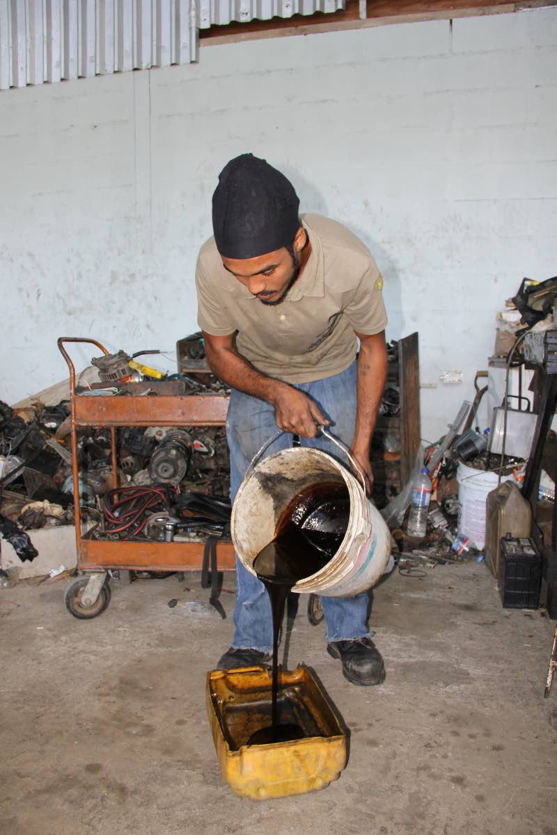 A man pours waste oil into a container at a garage.
