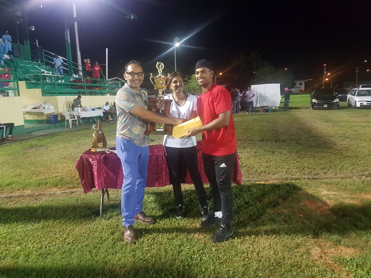 Winners' Nicholas Pooran, right, collects the league trophy from sponsor Vasant Bharath, left, as Bamboo Cricket League PRO Flora Maharaj, centre, looks on.