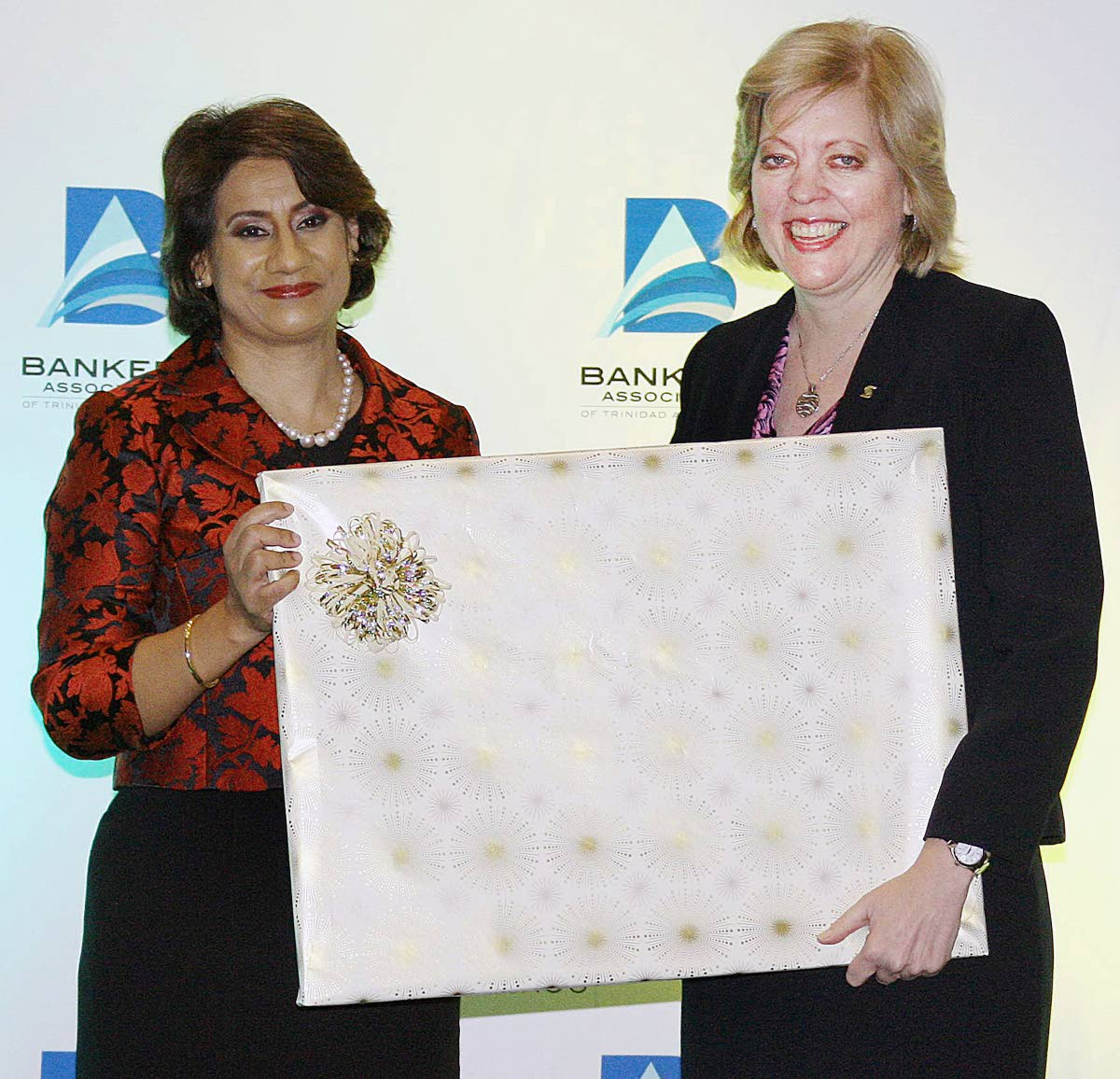 New Vice-President of the Bankers Association of TT (BATT), Karen D'arbasie, presents a gift to outgoing BATT President, Anya Schnoor, at a function on November 1, 2017 during BATT's 20th anniversary celebration at Hyatt Regency, Port of Spain. PHOTO COURTESY BATT