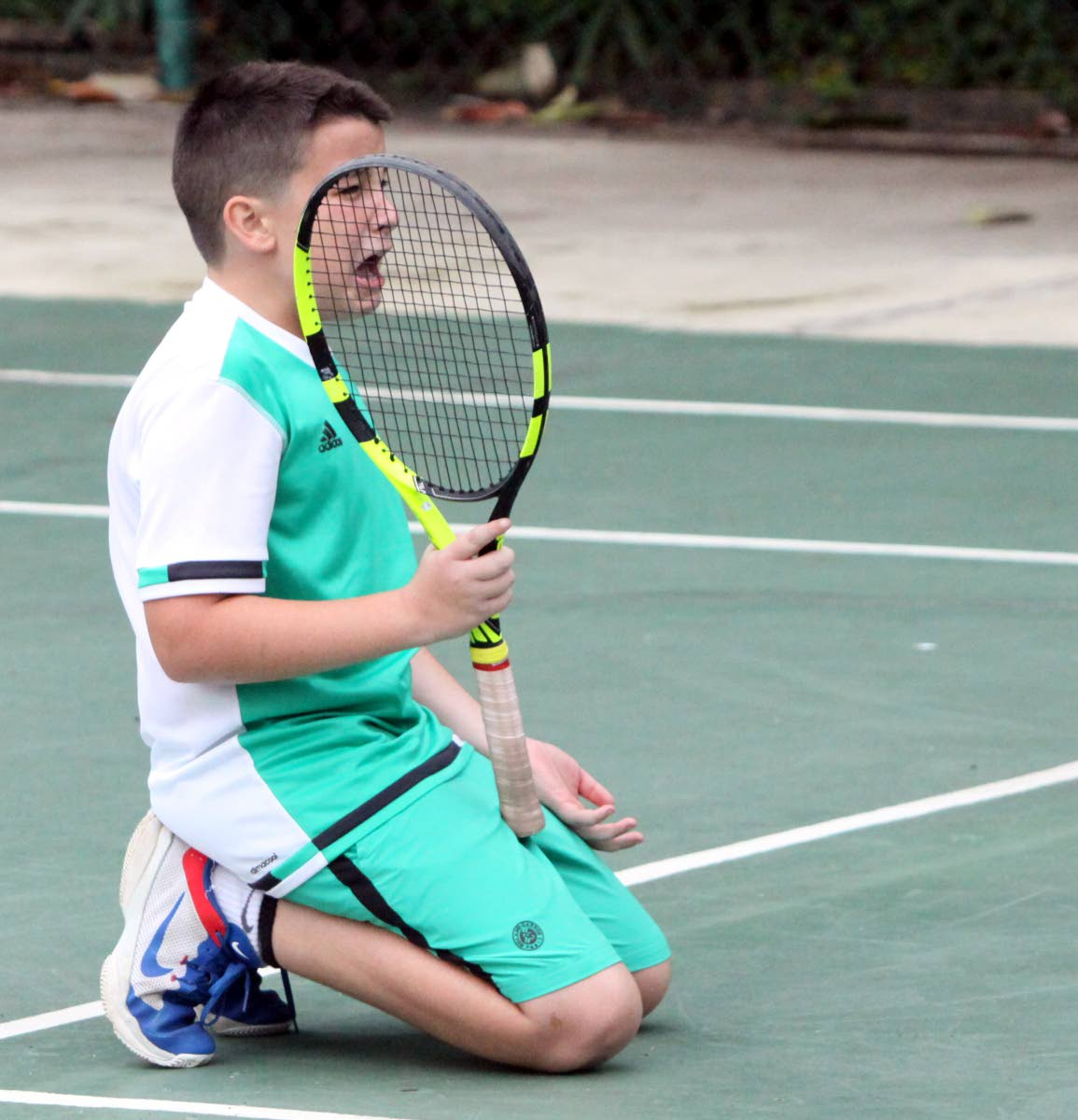 Declan Sheppard gets emotional in a boys Under-12 singles match against Alexander Merry at the Subway Junior Tennis Tournament at the Trinidad Country Club in Maraval, on Friday. Merry won the quarterfinal match 4-5, 4-1, 10-8.