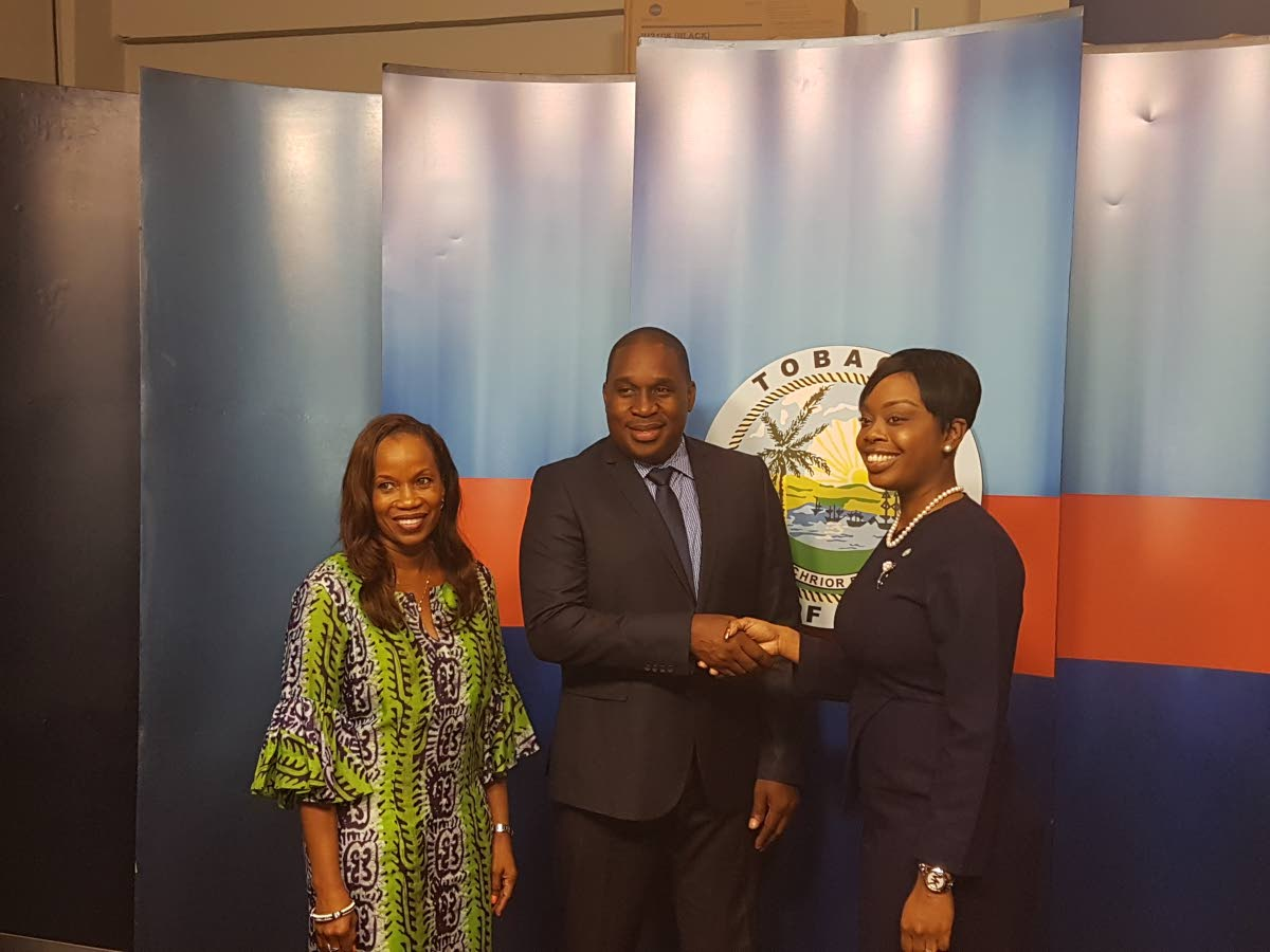 Secretary of Tourism, Culture and Transportation Nadine Stewart-Phillips, right, congratulates new chief executive officer of the Tobago Tourism Agency (TTA) Louis Lewis, as TTA chairman, Dr Sherma Roberts looks on.