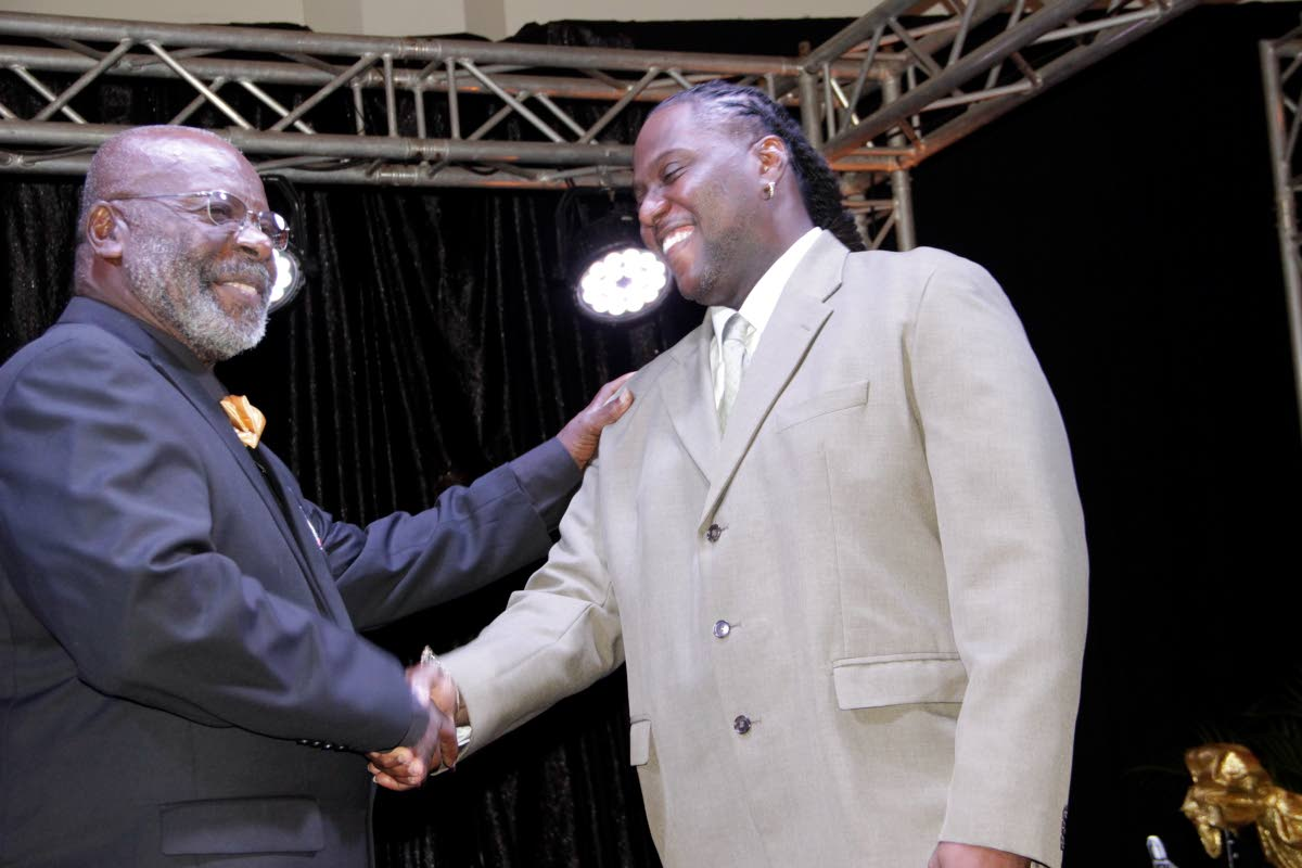   Sion Gomez, arranger for Buccooneers Steel Orchestra, who assisted the band with winning its 2013 Panorama title, in congratulated by founding father Charlie Murray at the band's 50th anniversary celebrations on Saturday at the Magdalena Grand Beach and Gold Resort in Lowlands
