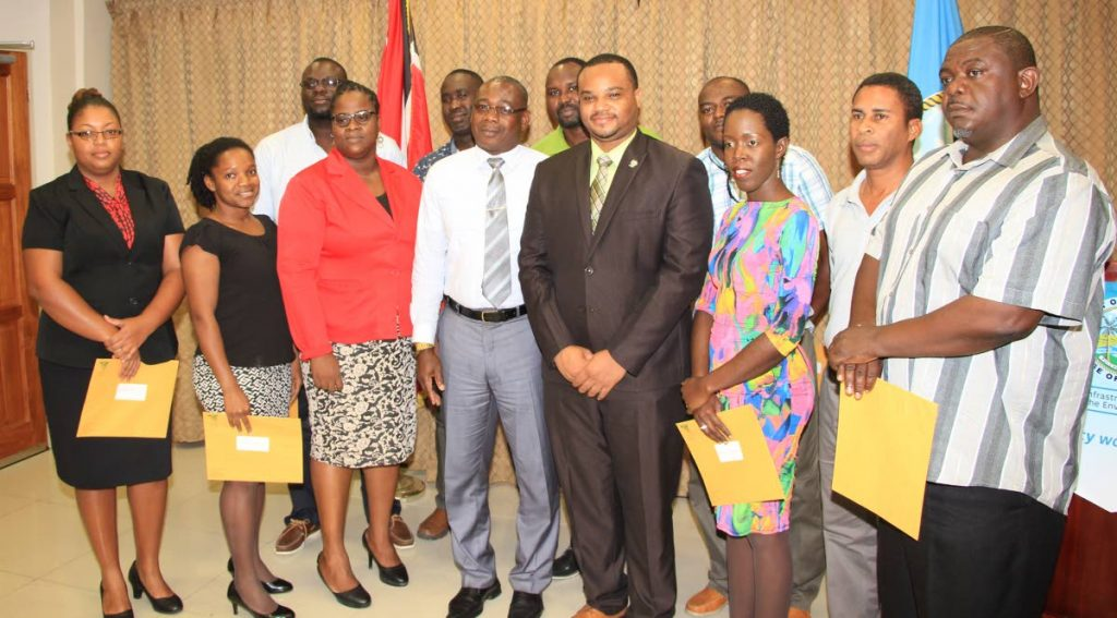 Food Production Secretary Hayden Spencer, front row, fourth from left, and Environment Secretary Kwesi Des Vignes, fifth from left, front row, pose for a photo with Environment Programme Officer II, Environmental Management Agency, Gillian Stanslaus third from left, from row, and environmental officers were received their instruments of appointments on November 2, from left, front row, Shivonne Peters, Aleisha Simpson, Jenise Kirk, Terrence Holmes, and in back row, from left, Kirth Mc Pherson, Kirwin Sampson, Garth Ottley, Darren Henry, and Robert De Matas.