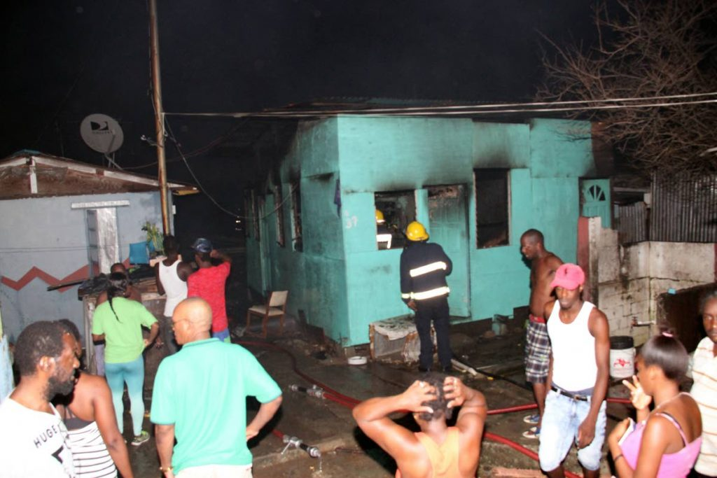 DESTROYED: Residents of Sea Lots look on in shock after several houses were destroyed in a fire late yesterday evening.  Approximately 45 people have been left homeless.    PHOTO BY SUREASH CHOLAI