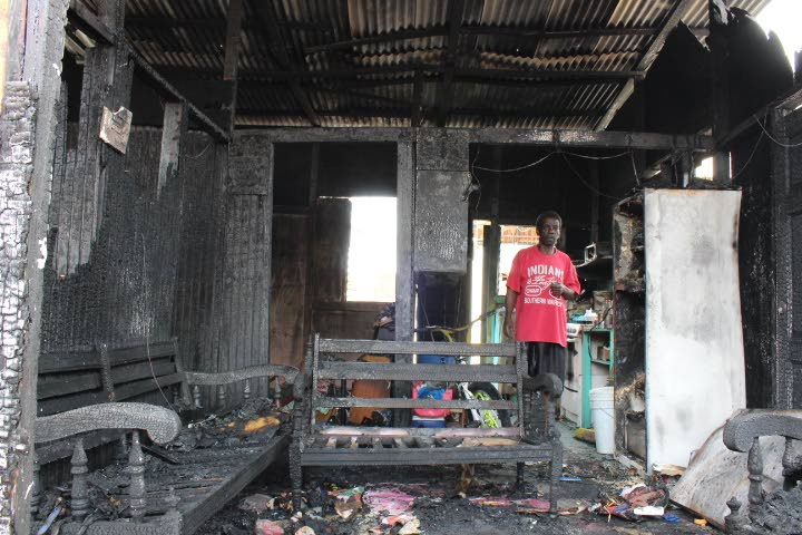 Francis Frederick stands in the burnt-out shell of his house at Sea Lots, Port of Spain, yesterday.