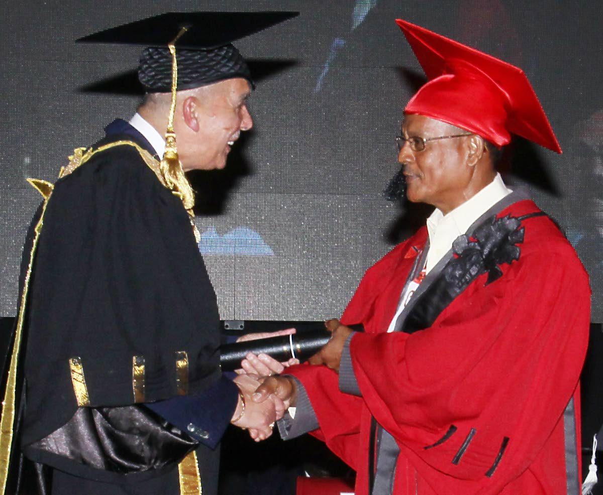 Chief honoured: President Anthony Carmona congratulates Santa Rosa First People's Chief Ricardo Bharath on his Honorary Distinguished Fellow award at UTT's graduation, O'Meara campus on Wednesday. PHOTO BY ANGELO MARCELLE