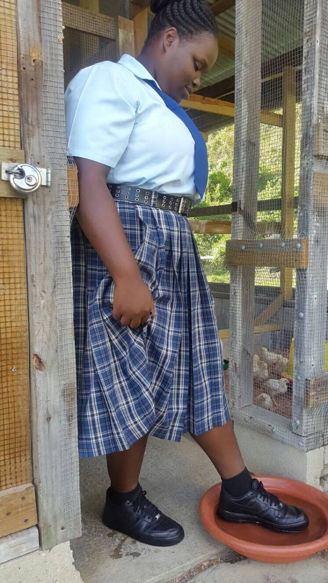 Chrisann McKenzie, top student in the CAPE Agricultural Science exam for 2017, washes her feet before heading into the chicken pens at the Agriculture Department at Speyside High School.
