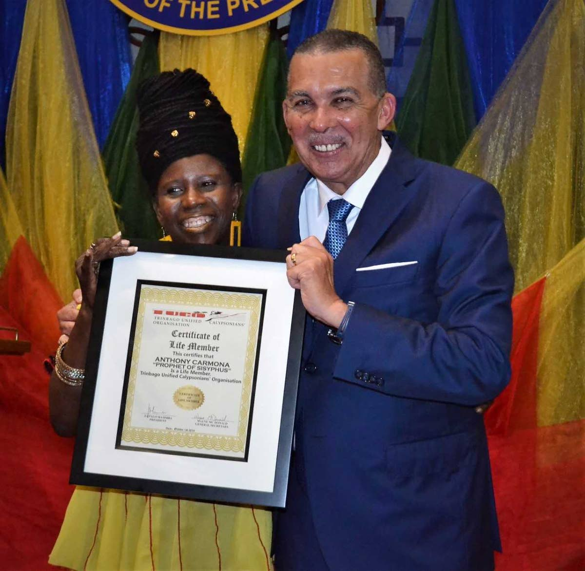 President Anthony Carmona receives the Certificate of Life Membership from Twiggy.