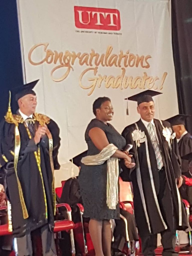 Queweina Roberts, daughter of Aldwyn Kitchener Roberts is congratulated by Professor Sarim Al-Zubaidy, UTT President after receiving the honorary doctorate certificate on behalf of her father. At left is UTT Chancellor and President of the Republic of Trinidad and Tobago, Anthony Carmona.