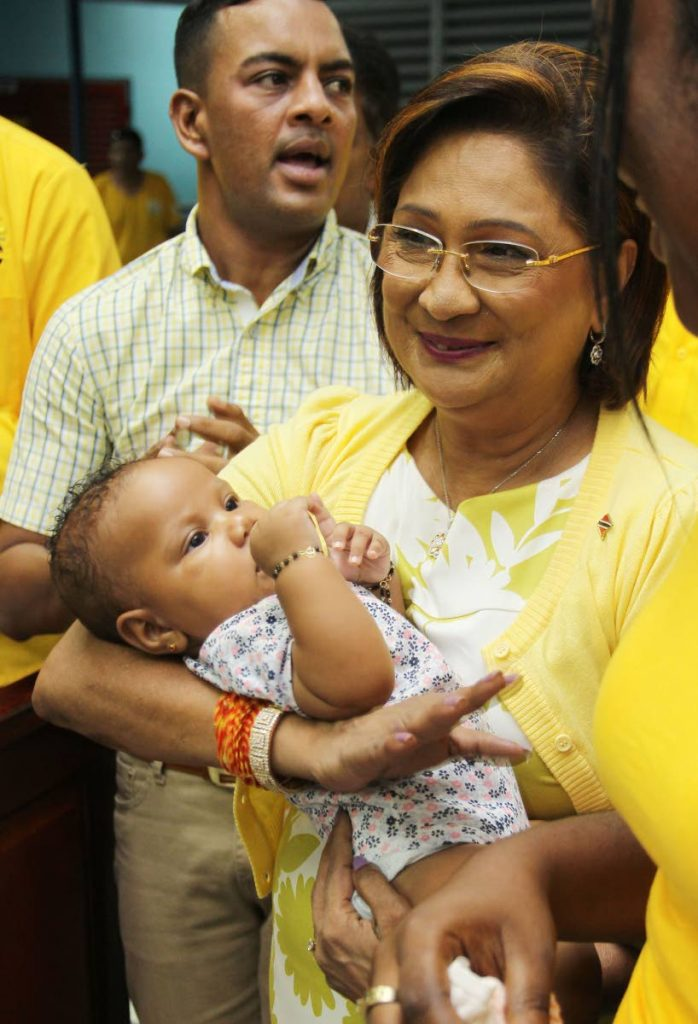 NICE BABY: Political leadef of the UNC Kamla Persad-Bissessar holds three- month-old Kimmie Ockille at a cottage meeting held at the Rio Claro Presbyterian school.