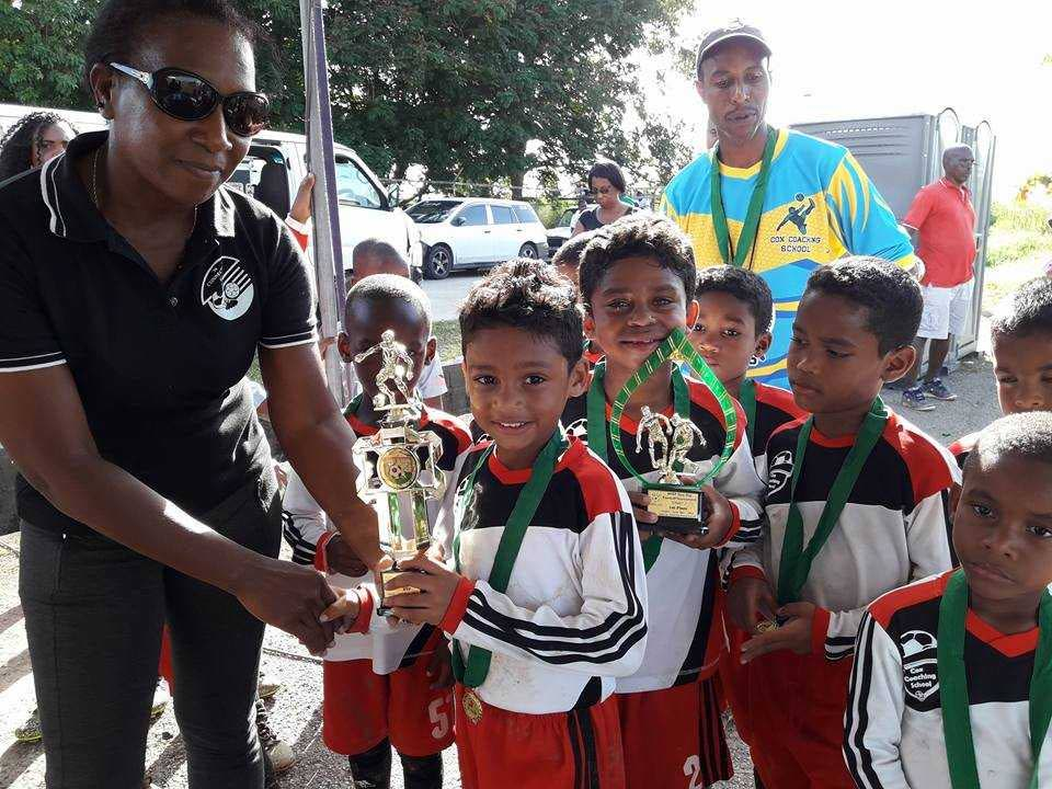 Cox Coaching School footballers collect their trophy and medals after topping the Under-7 age group at the Waterloo Institute of Soccer Players annual football fiesta recently.