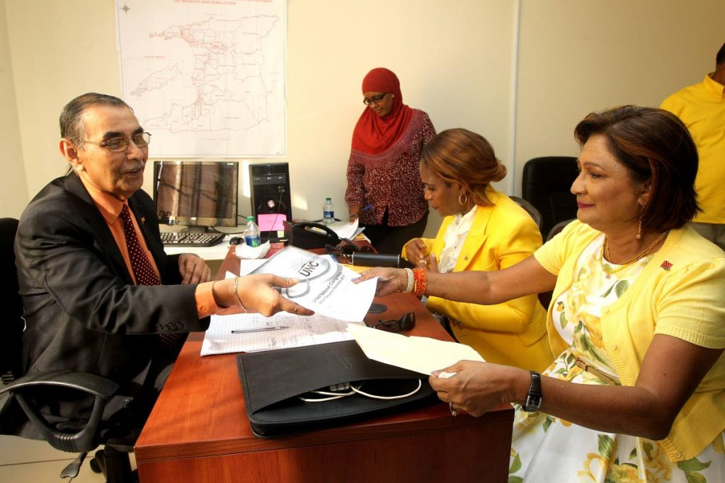 DEPUTY ESSENTIAL: Opposition Leader  Kamla Persad-Bissessar, right, presents nomination papers to contest the post of political leader of the UNC, to election officer Dr Rampersad Parasram. Next to her is former HDC head Jearlean John who also  presented papers for the post of deputy political leader at the party's headquarters in Couva yesterday. PHOTO BY LINCOLN HOLDER
