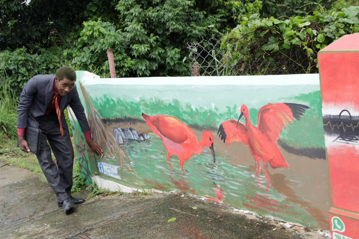 Artist Foster Isaac stands next to his mural of the Scarlet Ibis on a wall in Calder Hall.