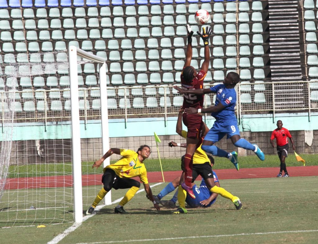 Naparima Boys' Jeron Pantor, right, challenges St Benedict's goalie Isiah Williams for the ball in a Coca Cola South Intercol semi-final yesterday at the Manny Ramjohn Stadium, Marabella.