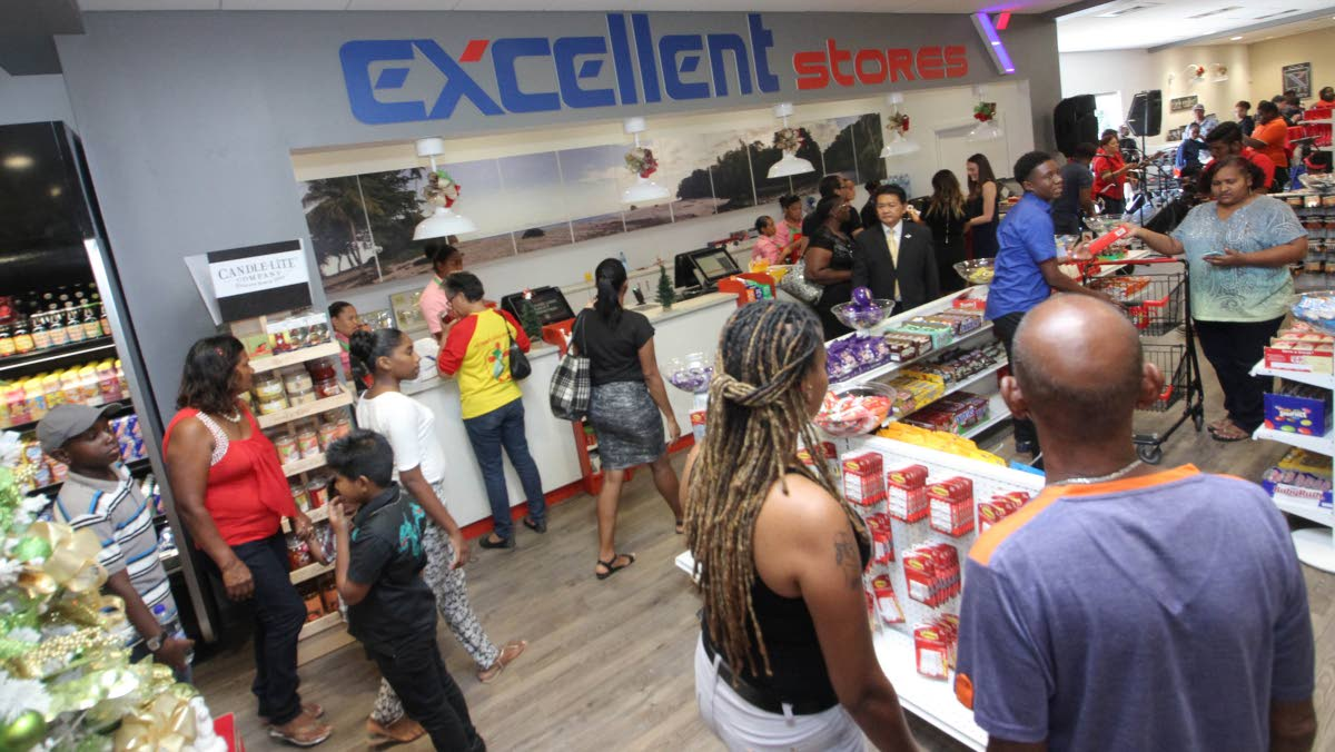 Franco Siu Chong, centre right, looks on as customers experience the grand opening of Excellent Stores' new location in the Shops of Arima complex, Tumpuna Road, Arima, yesterday.
