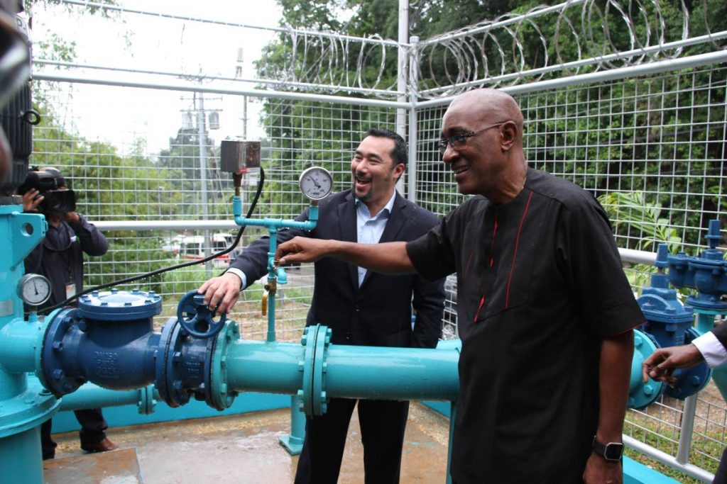 Public Utilities Minister Robert Le Hunte, right, together with Minister in the Office of Prime Minister Stuart Young open the valves of the new WASA Mc Kai Booster Station off the Lady Young Road in Belmont. PHOTO SUREASH CHOLAI