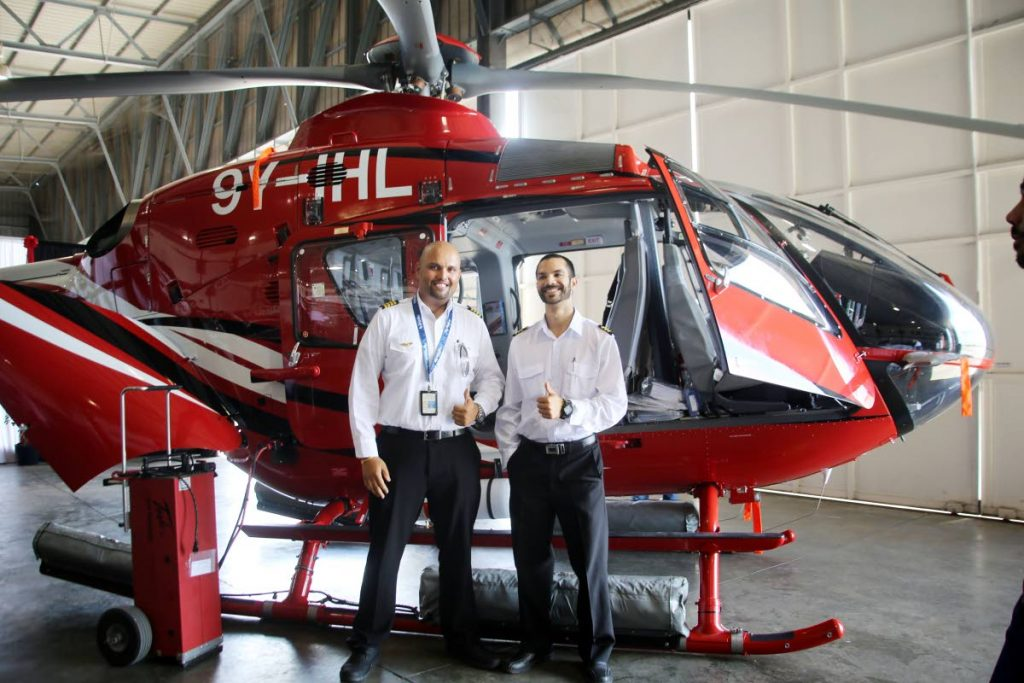 These two National Services Helicopter pilots, Shivan Rampersad, left, and Spencer Forcette, right, stand by one of the new helicopters during a media launching at the NHSL Heliport at Camden, Couva, yesterday. PHOTO BY VASHTI SINGH