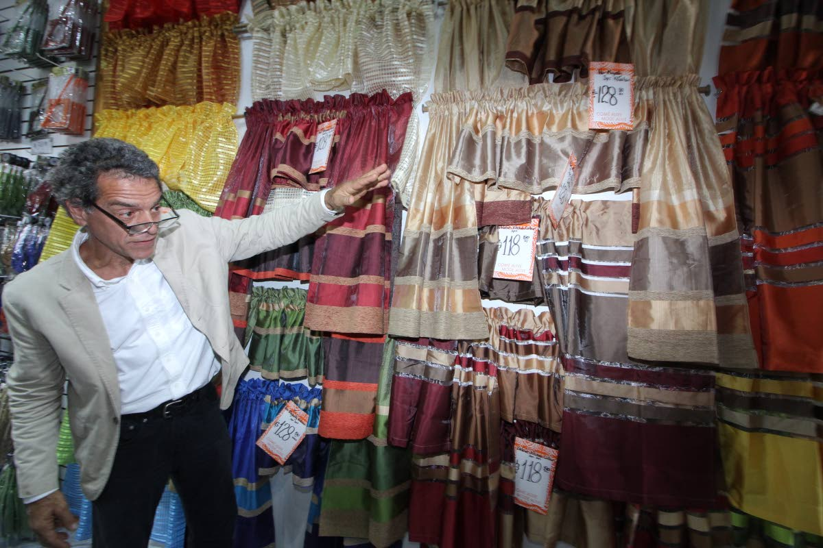 Mode Alive CEO Gary Aboud shows off some of the items he has on sale at his newly-reopened Valsayn branch yesterday.