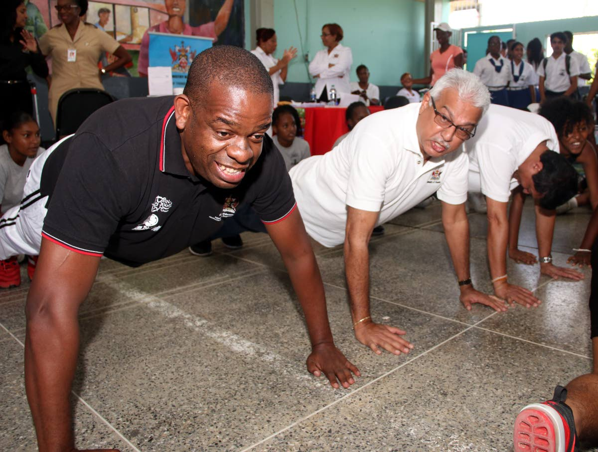Minister in the Ministry of Education Dr Lovell Francis, left, along with Minister of Health Terrence Deyalsingh, centre, and MP for fyzabad Dr Lackram Bodeo do push ups at the Fyzabad Anglican Secondary School yesterday.