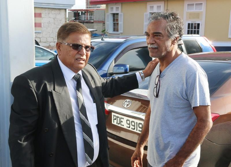 Dr Ronald Budhooram and his attorney Subhas Panday on July 14 after his release from police custody. Police last night reported Dr Budhooram has been charged with manslaughter in the death of a baby boy in July.
