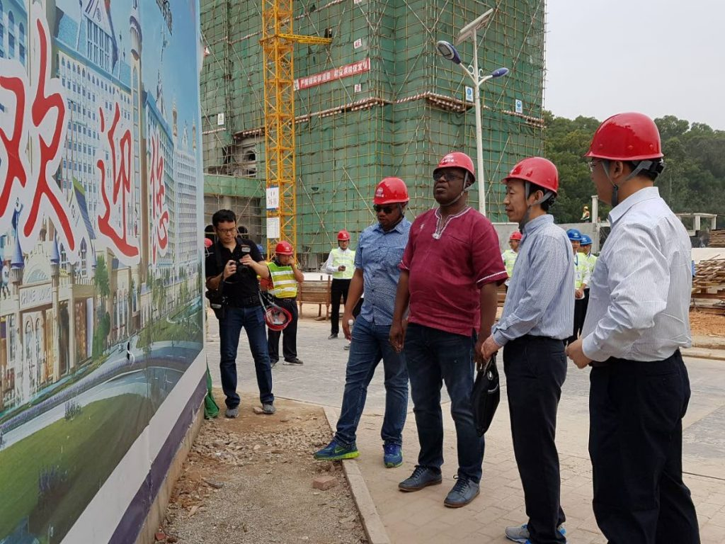 THA Chief Secretary Kelvin Charles, second from left, and Secretary of Infrastructure, Kwesi Des Vignes, left, look at a design of a project by a team from the China Railway Construction Company (CRCC) during their visit for the China-Latin America and the Caribbean (CLAC) International Exposition in Zhuhai recently.  .