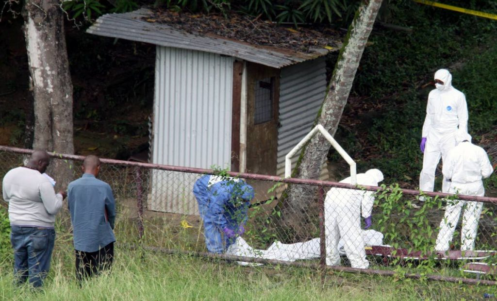 CRIME SCENE: Police at the Morvant Recreation ground yesterday where two men were found shot to death. PHOTO BY ANGELO MARCELLE