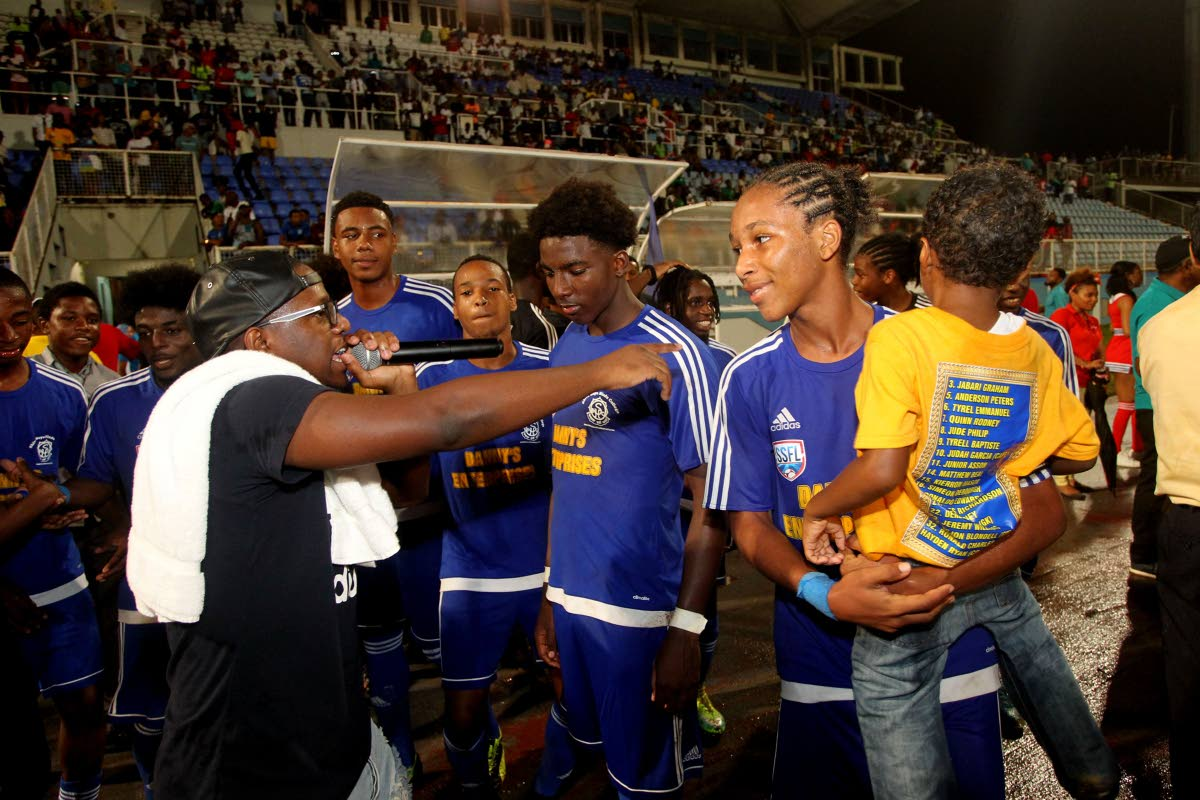 Soca Monarch champion Aaron 'Voice' St Louis, left, sings to newly crowned Coca Cola Intercol champs Shiva Boys after their 2-0 win over San Juan North in the final on Monday at the Ato Boldon Stadium, Couva.