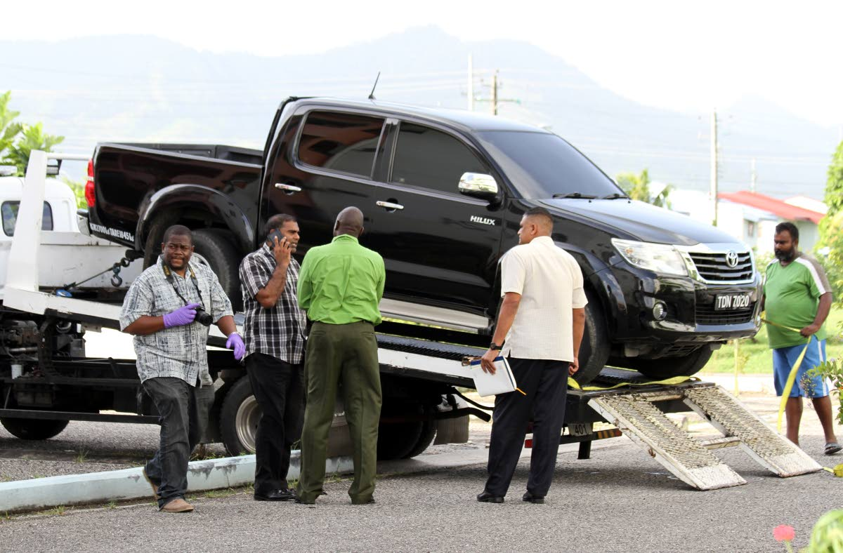 EVIDENCE: Police near a heavily tinted pick-up van which they believe was used in a daring $5 million hold-up by bandits at Piarco International Airport. PHOTO BY SUREASH CHOLAI