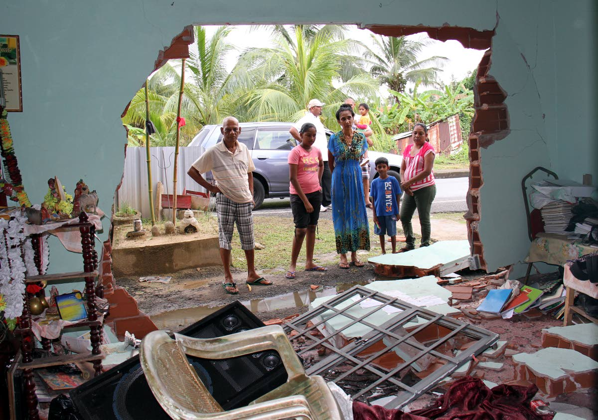 "CLEAR VIEW: At centre, house owner Vijanti Seudath and tenants look at the damaged done after a driver who ""lost control"" of his car and slammed into the house at Wellington Road, Debe."
