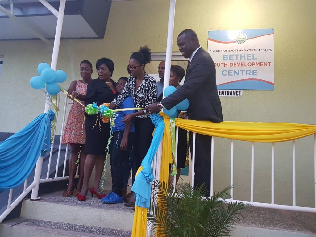Secretary of Community Development Marslyn Melville Jack, second from left, and Assistant Secretary Shomari Hector, right, look on as Youth Centre Coordinator, Division of Youth, Janice McMillan, cuts the ribbon to formally re-open the Bethel Youth Development Centre last Thursday.