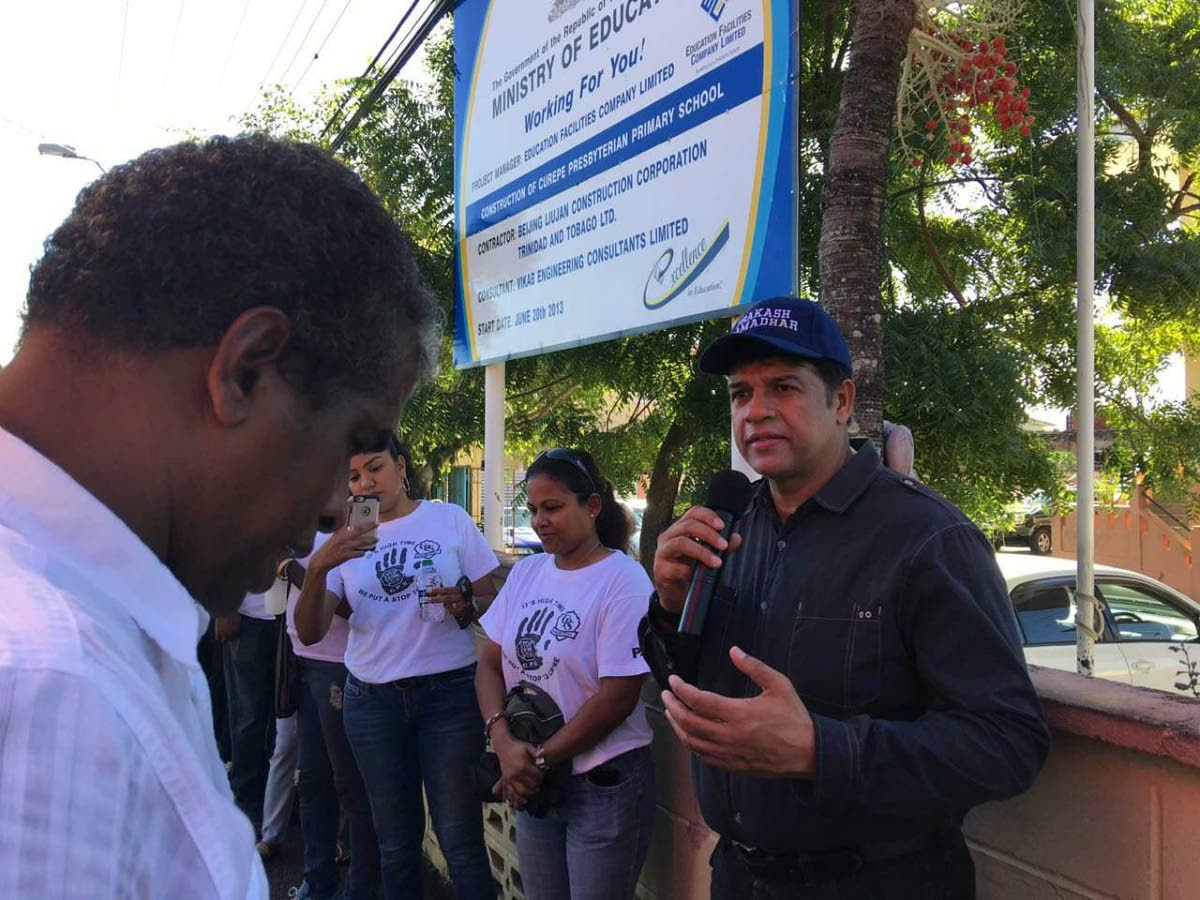 St Augustine MP Prakash Ramadhar (right) speaks during a prayer walk yesterday with the PTA of the Curepe Presbyterian School.