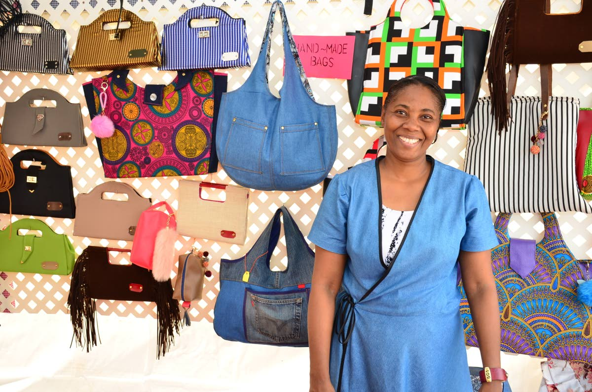 Claudette Daniel shows off he handmade bags at her booth at the Christmas Village on the Milford Road Esplanade on Monday.