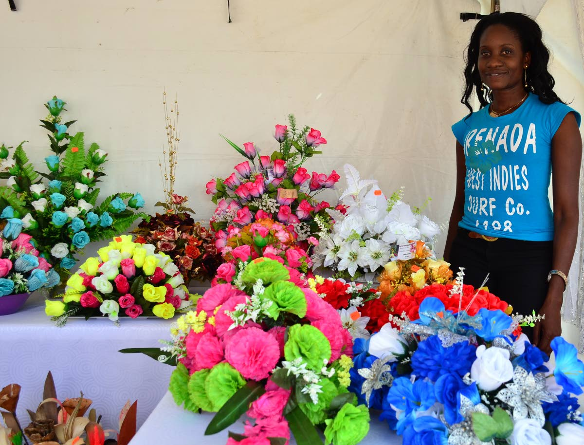 Portia George shows off her range of silk flowers at the Christmas Village on the Milford Road Esplanade on Monday.