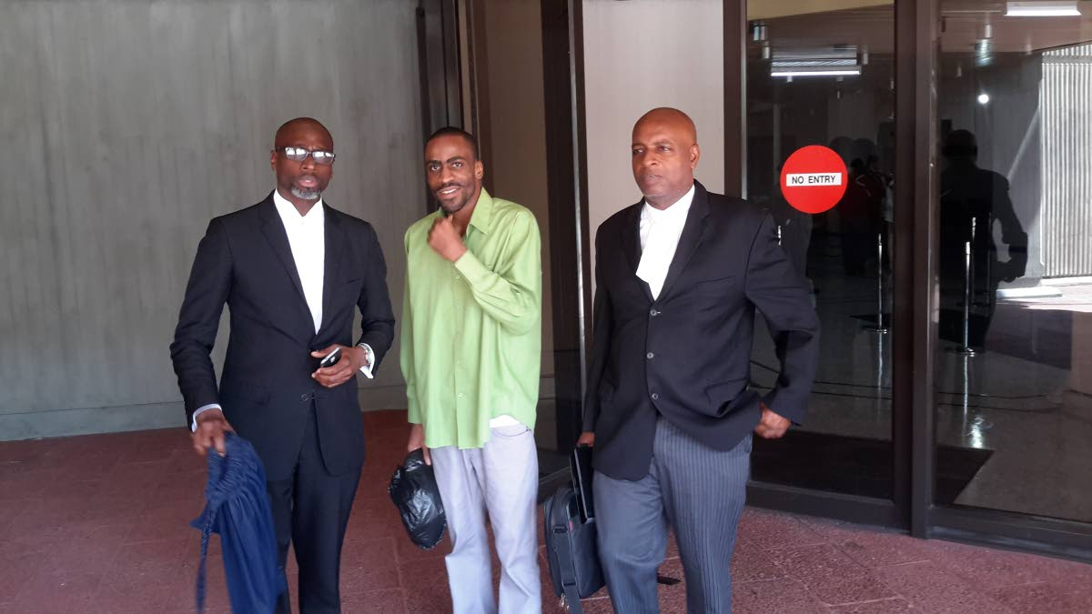 Dwayne Bramble, at centre, who was freed of a murder charge, leaves the Hall of Justice, Port of Spain, with his attorneys Kelston Pope, left, and Evans Welch, right.