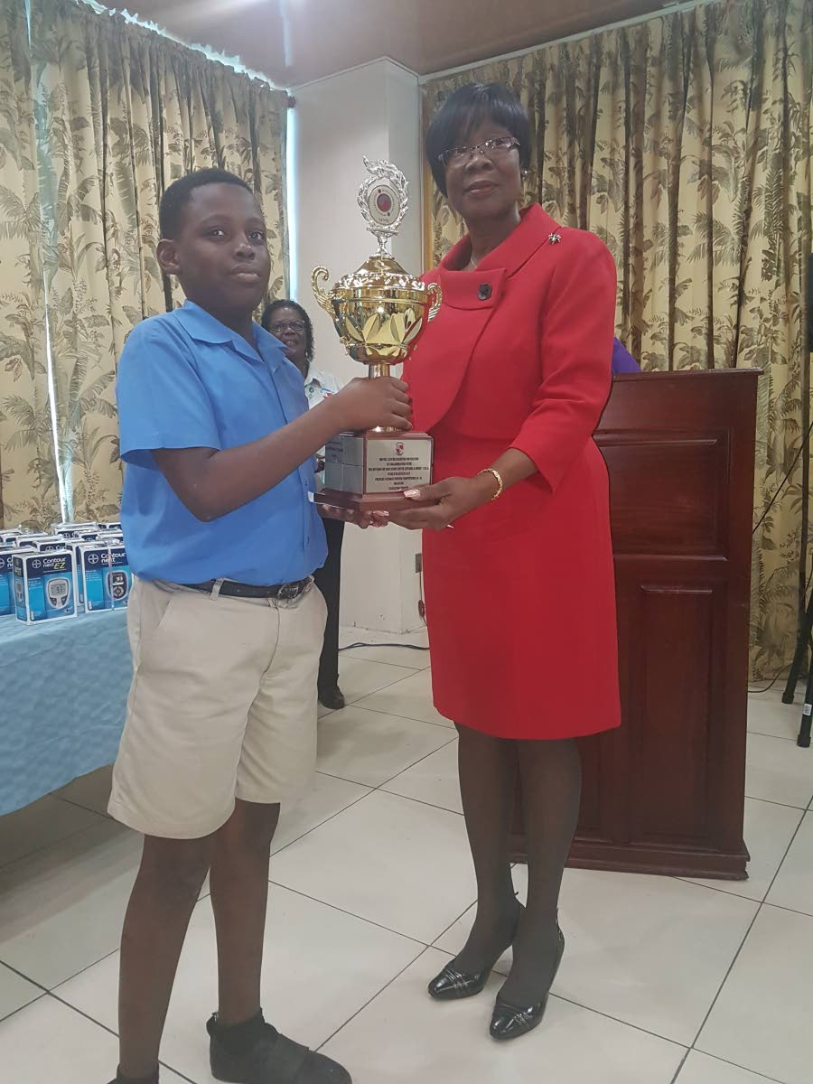 Rondell Daniel of Delaford Anglican Primary School collects his prize from Dr Agatha Carrington, Secretary for Health, as a participant in the 6-9 age group in the drawing category of the World Diabetes Day poster competition hosted by the Bovell Cancer Diabetes Foundation.