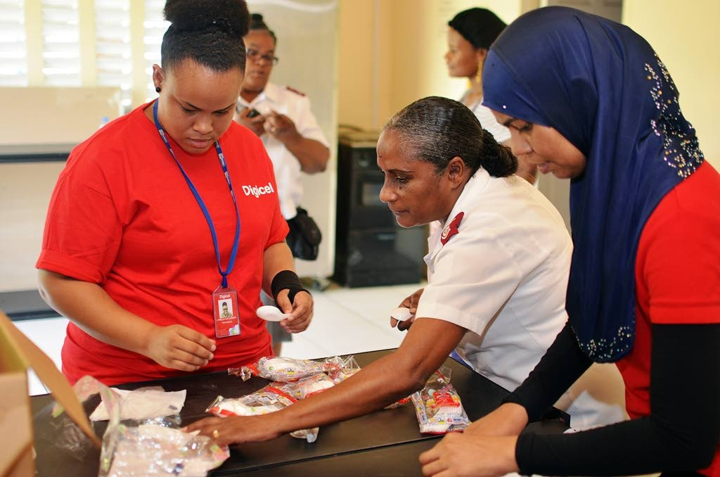 Digicel employees help Major Harry from the Salvation Army with the Annual Soup Feeding outreach.