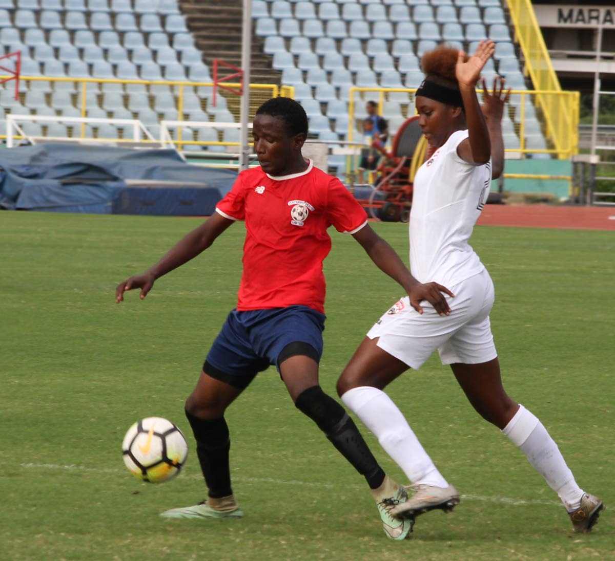 Trinidad and Tobago women's Under-20 player Kedie Johnson, right, defends as Jamal Durant of a North Under-15 boys team shields the ball in a practice match held recently at the Hasely Crawford Stadium, Mucurapo.