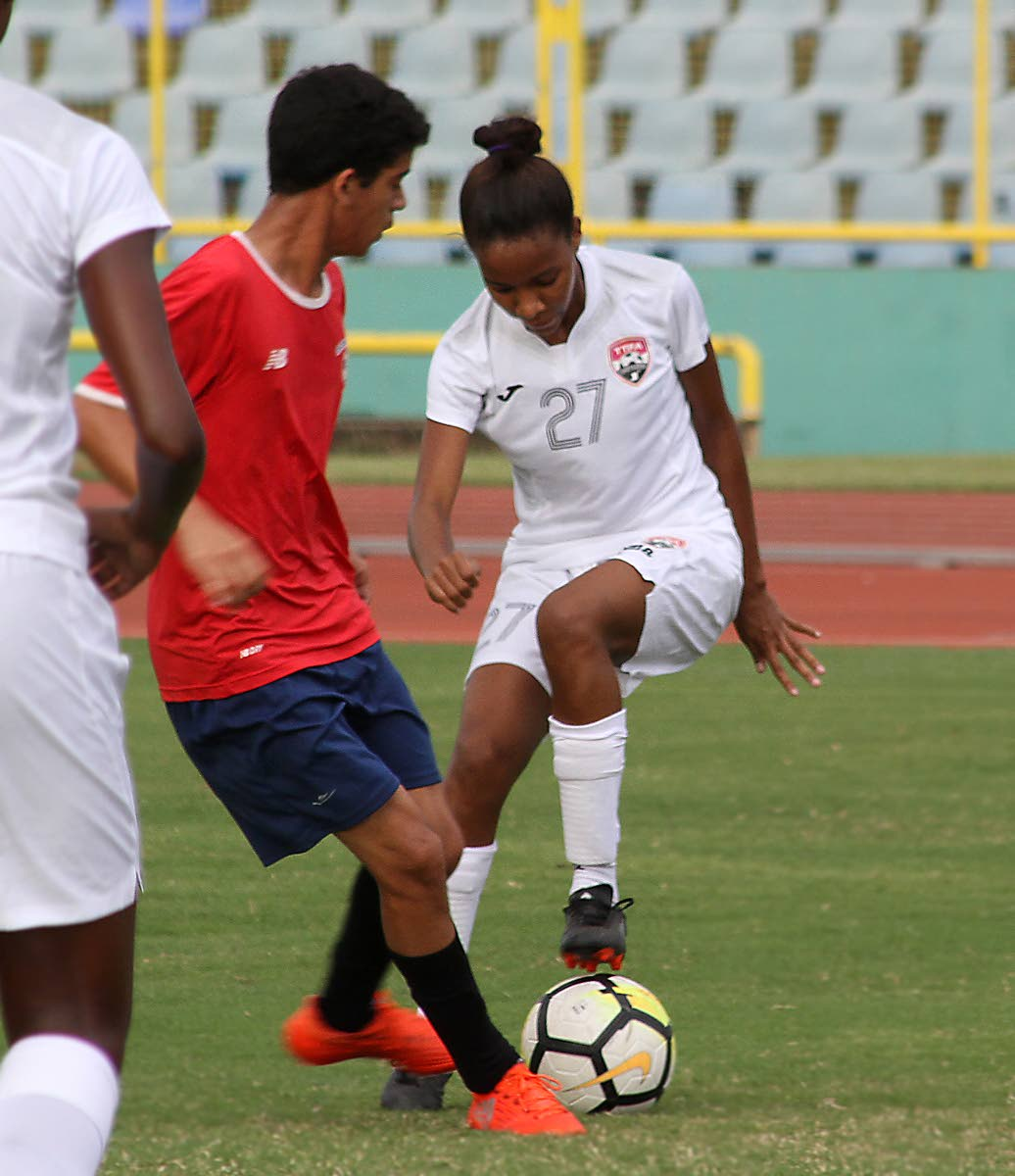 Trinidad and Tobago's Raynicia Charles, right, on the ball against Andrew De Gannes in a friendly match between the national women's Under-20 team vs a North U-15 boys team at the Hasely Crawford Stadium, Mucurapo.