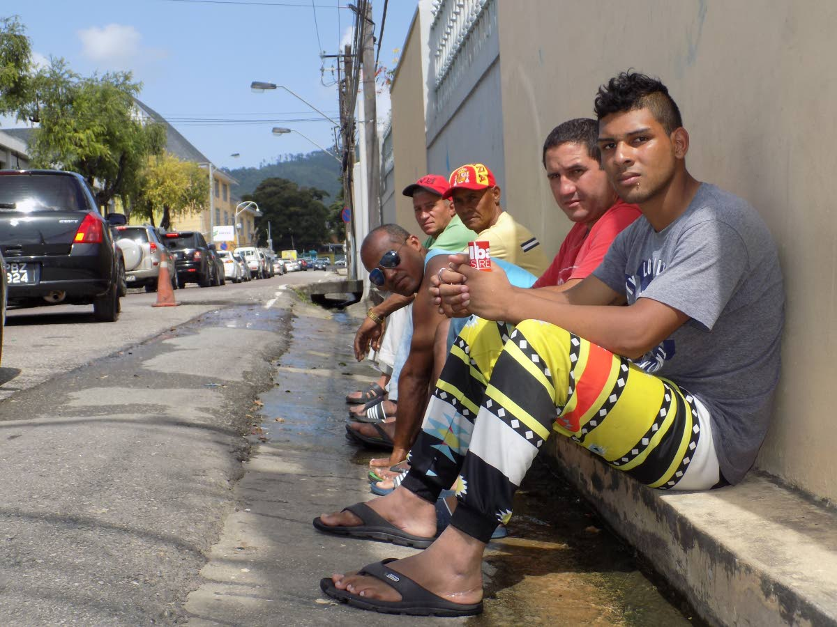 File Photo: Yusnell Perez, first from right and four other Cuban nationals sit over a drain just outside the United Nations Regional Office at Chancery Lane, Port of Spain.  PHOTO BY SHANE SUPERVILLE